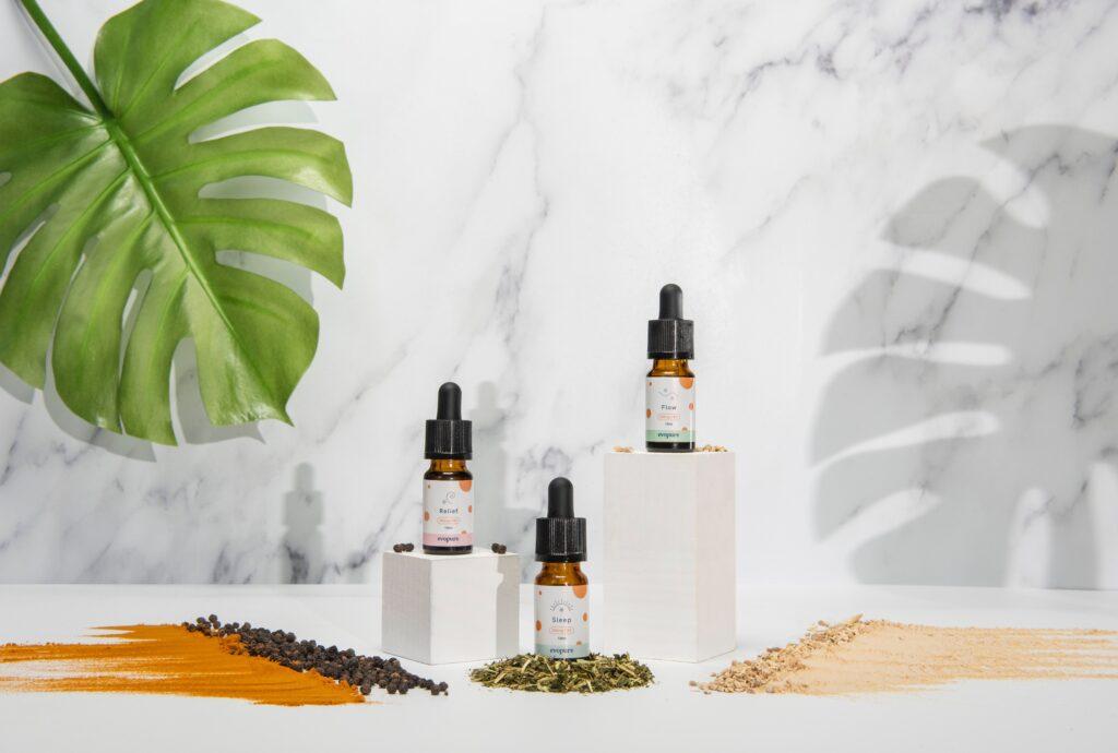 three bottles of cbd oil on a white table